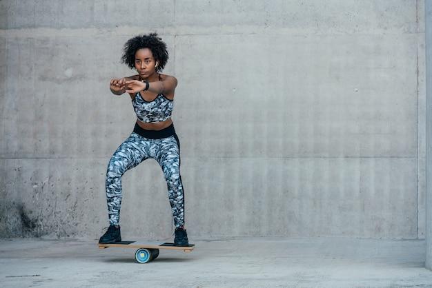 屋外でスクワットレッグをエクササイズしてやっているアフロアスリート女性。スポーツと健康的なライフスタイルのコンセプト。