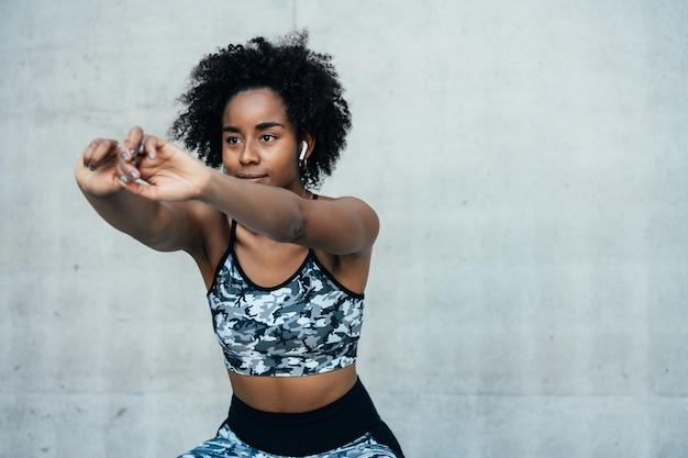 屋外で運動する前にストレッチとウォーミングアップを行うアフロアスリート女性。スポーツと健康的なライフスタイル。