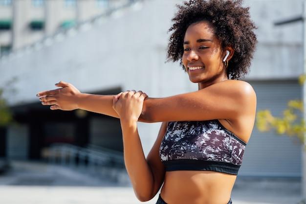 屋外で運動する前に腕を伸ばしてウォーミングアップするアフロアスリート女性