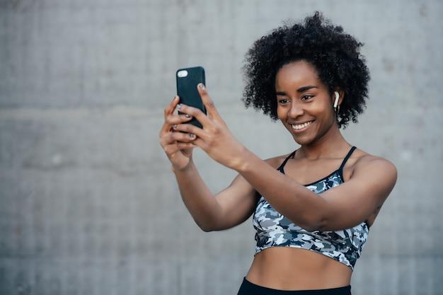 屋外で運動した後、携帯電話で自分撮りをしているアフロアスリート女性。スポーツと健康的なライフスタイル。