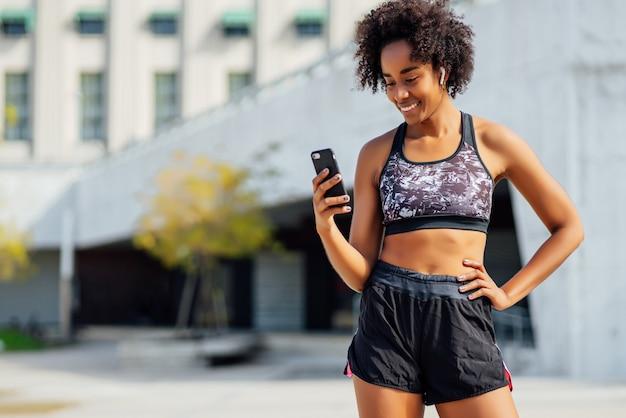 携帯電話を使用し、屋外で運動した後にリラックスするアフロアスリートの女性。スポーツと健康的なライフスタイルのコンセプト。