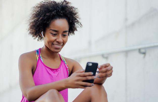 携帯電話を使用し、屋外で運動した後にリラックスするアフロアスリートの女性。スポーツとテクノロジーのコンセプト。