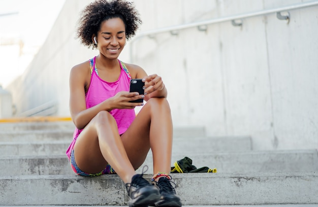 携帯電話を使用し、屋外で運動した後にリラックスするアフロアスリートの女性。