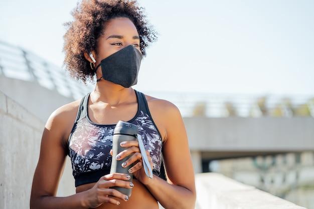 屋外で運動した後、フェイスマスクを着用し、水のボトルを保持しているアフロアスリートの女性。新しい通常のライフスタイル。スポーツと健康的なライフスタイル。