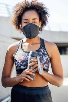 屋外で運動した後、フェイスマスクを着用し、水のボトルを保持しているアフロアスリートの女性。スポーツと健康的なライフスタイル。