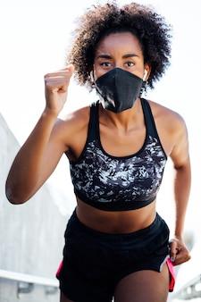 屋外で走っている間フェイスマスクを身に着けているアフロアスリート女性。新しい通常のライフスタイル。スポーツと健康的なライフスタイルのコンセプト。