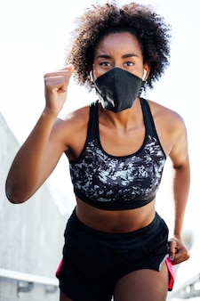 Afro athletic woman wearing face mask while running outdoors. new normal lifestyle. sport and healthy lifestyle concept.
