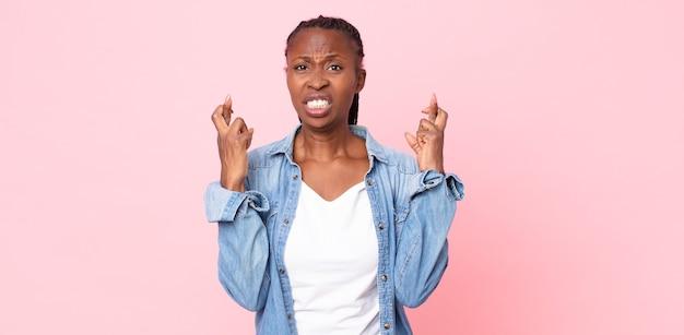 아프로 흑인 성인 여성이 걱정스럽게 손가락을 교차하고 걱정스러운 표정으로 행운을 빕니다