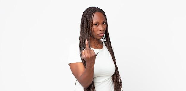 아프로 흑인 성인 여성은 화가 나고 짜증이 나고 반항적이고 공격적이며 가운데 손가락을 뒤집고 반격합니다.