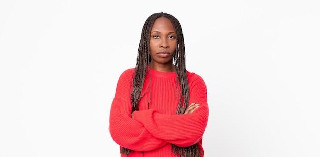 アフロ黒人の大人の女性は、不満と失望を感じ、深刻に見え、イライラし、腕を組んで怒っています