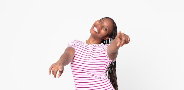 Афро-черная взрослая женщина чувствует себя счастливой и уверенной, указывая на камеру обеими руками и смеясь, выбирая вас