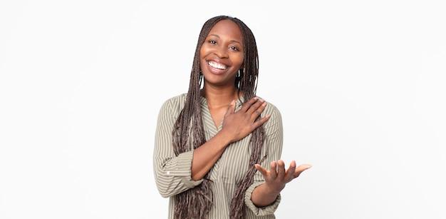 幸せで恋をしているアフロ黒人の大人の女性は、片方の手が心臓の横に、もう片方の手が前に伸びて笑っています