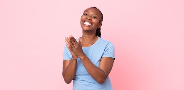 아프리카 흑인 성인 여성은 행복하고 성공적인 느낌을 받으며 박수로 축하하며 웃고 손뼉을 칩니다.
