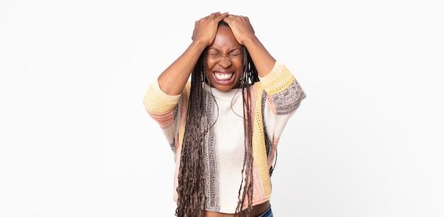 ストレスと不安を感じ、頭痛で落ち込んで欲求不満を感じ、両手を頭に上げているアフロ黒人の成人女性