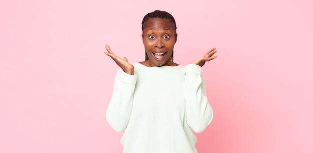 Афро-черная взрослая женщина выглядит счастливой и взволнованной, потрясенной неожиданным сюрпризом с открытыми руками рядом с лицом