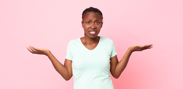 Afro black adult woman looking puzzled, confused and stressed, wondering between different options, feeling uncertain