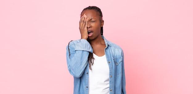 頭痛と片方の手が顔の半分を覆っている、眠くて退屈であくびをしているアフロ黒人の成人女性