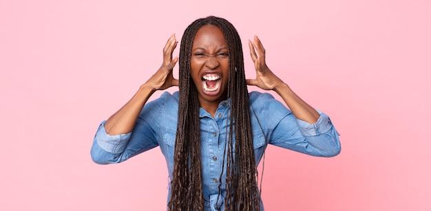 아프리카 흑인 성인 여성이 머리 옆에 손을 놓고 공황이나 분노로 비명을 지르며 충격을 받거나 겁에 질리거나 화를 내며