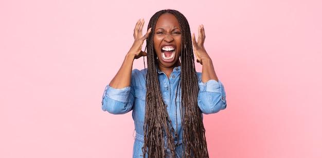 아프리카 흑인 성인 여성이 손을 높이 들고 비명을 지르며 분노하고, 좌절하고, 스트레스를 받고, 화가 났습니다.