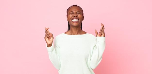 아프로 흑인 성인 여성은 웃고 걱정스럽게 두 손가락을 교차하며 걱정하고 행운을 빌거나 바라고 있습니다.