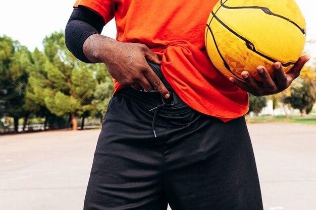 彼の銃を見せているアフロ黒人の男。バックグラウンドでアーバンバスケットボールコート。
