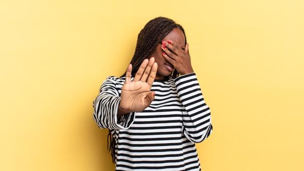 아프리카 흑인 예쁜 여성이 손으로 얼굴을 가리고 다른 손을 앞으로 올려 카메라를 멈추고 사진이나 사진을 거부합니다.