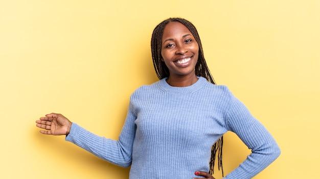 아프로 흑인 예쁜 여성은 행복하고 쾌활하며 미소를 지으며 당신을 환영하며 친근한 몸짓으로 당신을 초대합니다.