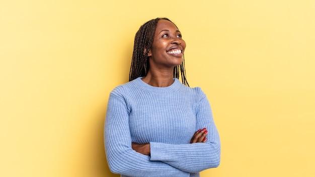 아프로 흑인 여성은 행복하고, 자랑스럽고, 희망적이고, 궁금하거나 생각하며, 팔짱을 끼고 공간을 복사하기 위해 올려다보고 있습니다.