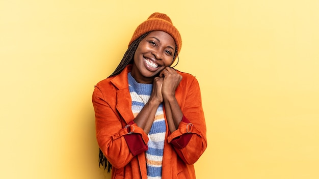 アフロ黒人のきれいな女性が恋をしていて、かわいくて、愛らしい、そして幸せそうに見えて、顔の隣の手でロマンチックに笑っています