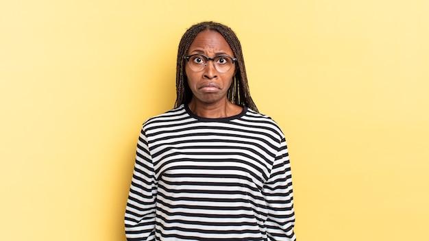 아프로 흑인 예쁜 여자는 슬프고 스트레스를 받고 부정적인 놀라움 때문에 화가 나고 부정적인 표정을 짓습니다.
