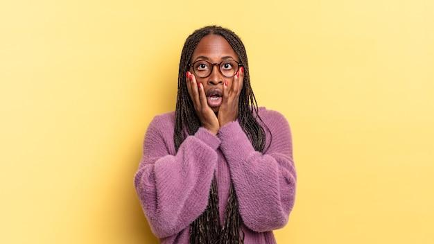 ショックと恐怖を感じ、口を開けて頬に手を当てて恐怖を感じているアフロ黒人のきれいな女性