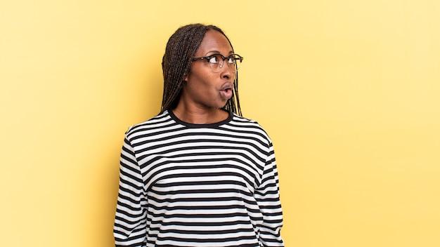 ショックを受け、幸せで、驚き、驚きを感じ、口を開けて横を向いているアフロ黒人のきれいな女性