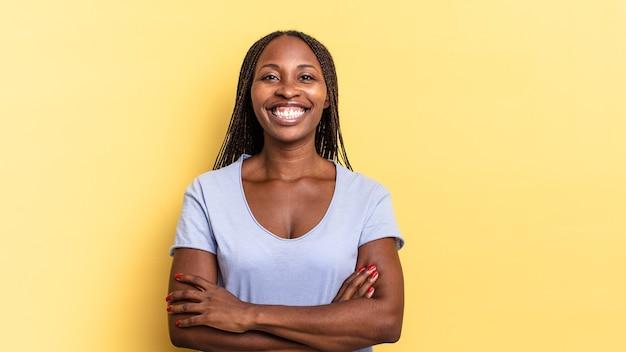 편안하고 긍정적이며 만족스러운 포즈로 팔짱을 끼고 행복하게 웃고 있는 아프리카 흑인 여성