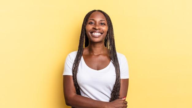 아프리카 흑인 예쁜 여자는 친절하고 긍정적이지만 불안한 태도로 수줍고 즐겁게 웃고 있습니다.