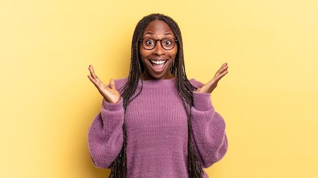 행복하고 흥분해 보이는 아프리카 흑인 예쁜 여자, 두 손을 얼굴 옆에 벌리고 예상치 못한 놀라움에 충격