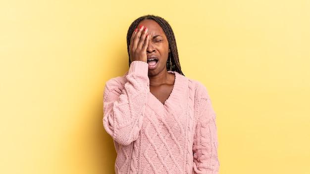 아프로 흑인 여성은 졸리고 지루하며 하품을 하고 두통과 한 손으로 얼굴의 절반을 덮고 있습니다.