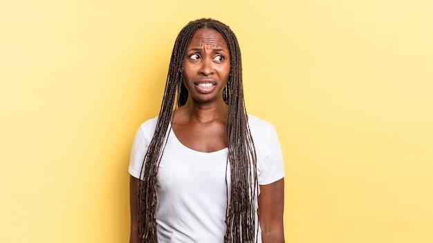 아프로 흑인 예쁜 여자는 걱정하고, 스트레스를 받고, 불안하고 무서워 보이고, 당황하고 이를 악물고 있습니다.
