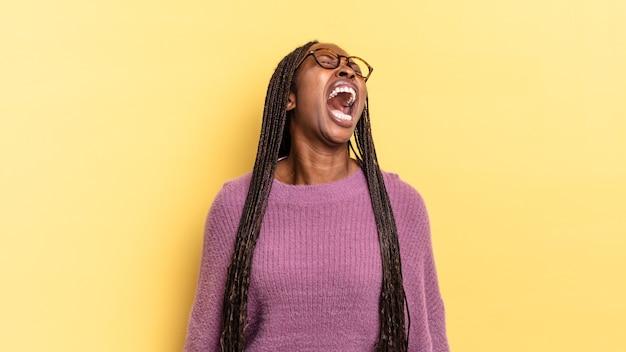 아프로 흑인 예쁜 여자는 격렬하게 비명을 지르며 공격적으로 소리를 지르며 스트레스를 받고 화난 것처럼 보입니다.