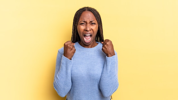 아프로 흑인 예쁜 여자는 짜증나고, 좌절하고, 화난 표정과 꽉 주먹으로 공격적으로 소리를 지르며 분노를 느낀다