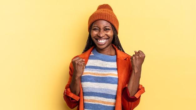 아프리카 흑인 예쁜 여성이 의기양양하게 외치고, 웃고, 성공을 축하하는 동안 행복하고 흥분됩니다.