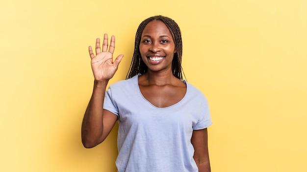 Афро-черная симпатичная женщина улыбается и выглядит дружелюбно, показывает номер пять или пятое с рукой вперед, отсчитывает