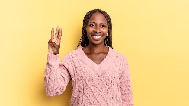 아프리카 흑인 예쁜 여성이 웃고 친근하게 보이며 손으로 3번 또는 3번을 앞으로 보여주며 카운트다운