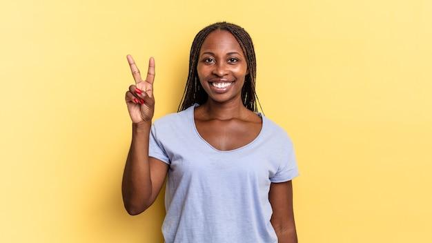 아프리카 흑인 예쁜 여성이 웃고 친근하게 보이며 손으로 2번 또는 2번을 앞으로 보여주며 카운트다운