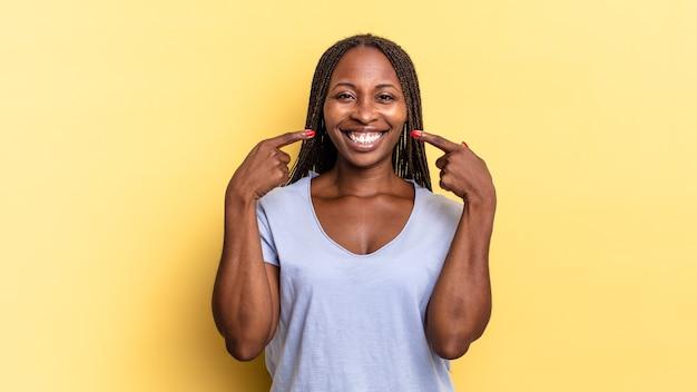 자신의 넓은 미소, 긍정적이고, 편안하고, 만족스러운 태도를 자신있게 가리키며 웃고 있는 아프리카 흑인 예쁜 여성