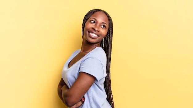 아프로 흑인 예쁜 여자는 즐겁게 웃고, 행복하고, 만족스럽고, 편안하며, 팔짱을 끼고 옆을 바라보고 있습니다.