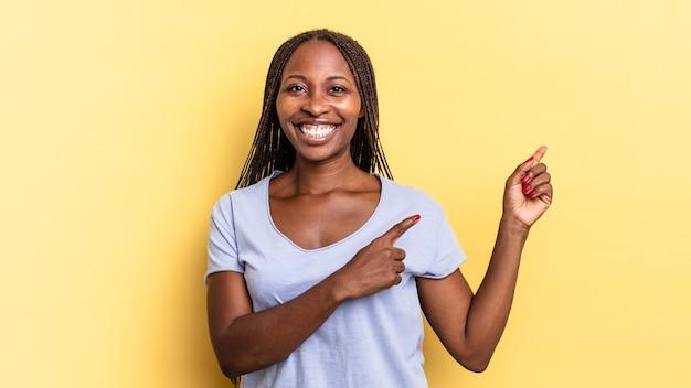 아프리카 흑인 예쁜 여성이 행복하게 웃고 복사 공간에 물건을 보여주는 양손으로 옆과 위쪽을 가리키고 있습니다.