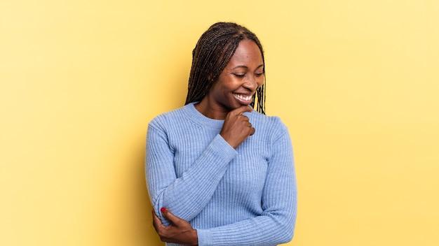 あごに手を当てて幸せで自信に満ちた表情で笑って、不思議に思って横を向いているアフロ黒人のきれいな女性