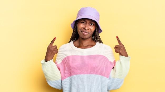 자랑스럽고 공격적으로 보이는 나쁜 태도, 위쪽을 가리키거나 손으로 재미있는 표지판을 만드는 아프리카 흑인 예쁜 여성