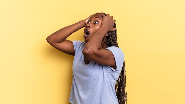 입을 벌리고 있는 아프로 흑인 예쁜 여자, 끔찍한 실수로 인해 겁에 질려 충격을 받은 것처럼 보이고 손을 머리에 들고