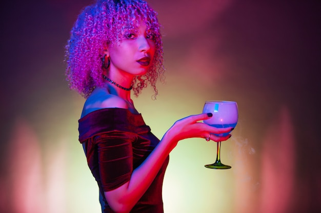 Afro black woman holding an alcoholic blue mystery drink